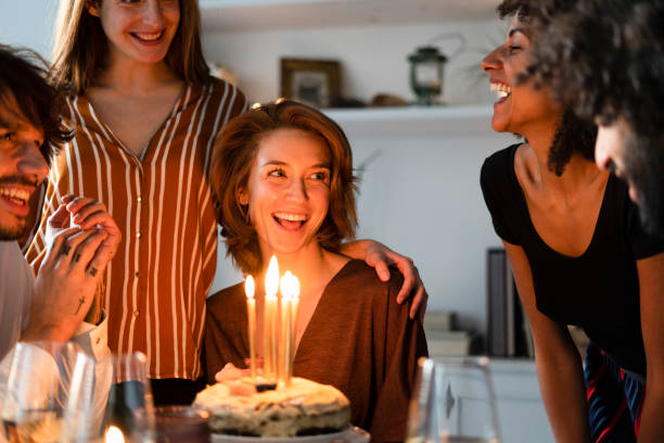 friends surprising young woman with a birthday cake with burning candles - best friend birthday cake stock pictures, royalty-free photos & images