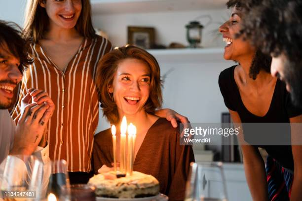friends surprising young woman with a birthday cake with burning candles - happy birthday stock pictures, royalty-free photos & images