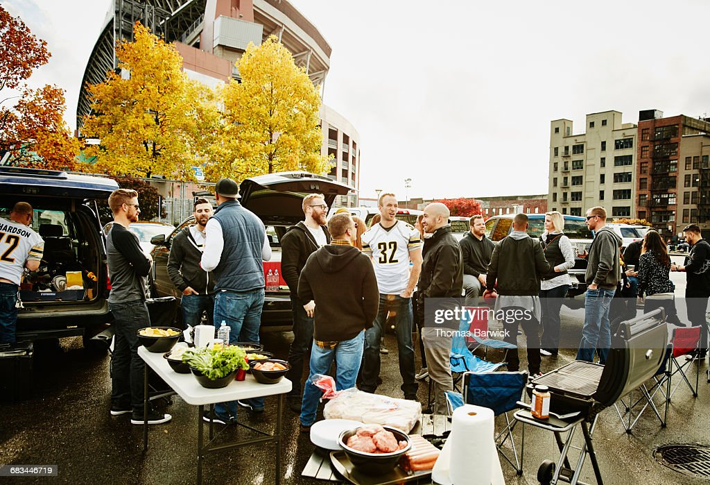 Friends tailgating in stadium parking lot : Stock Photo