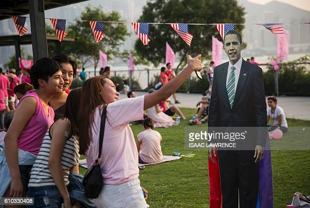 Friends take a selfie next to a cardboard cut out of US president Barack Obama at Pink Dot a lesbian gay bisexual transgender/transsexual and...