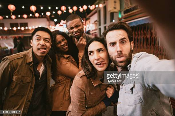 friends take selfie in chinatown downtown los angeles at night - organised group photo stock pictures, royalty-free photos & images