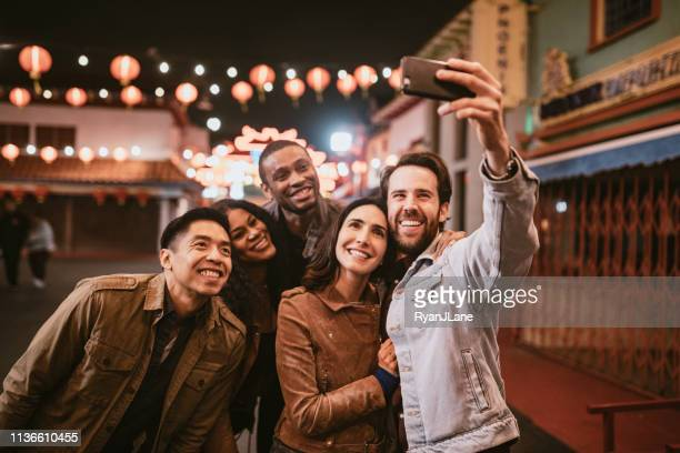 friends take selfie in chinatown downtown los angeles at night - city life stock pictures, royalty-free photos & images
