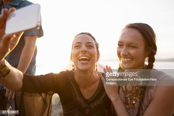 friends taking a self portrait on beach - photography stock pictures, royalty-free photos & images