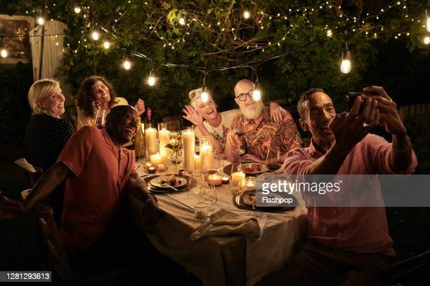 friends taking a self with a phone and dining outside on a warm summers evening. - {{relatedsearchurl(carousel.phrase)}} stock pictures, royalty-free photos & images
