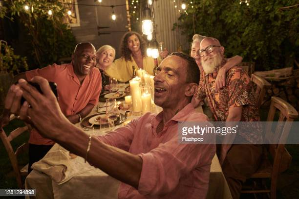 friends taking a self with a phone and dining outside on a warm summers evening. - candlelight stock pictures, royalty-free photos & images