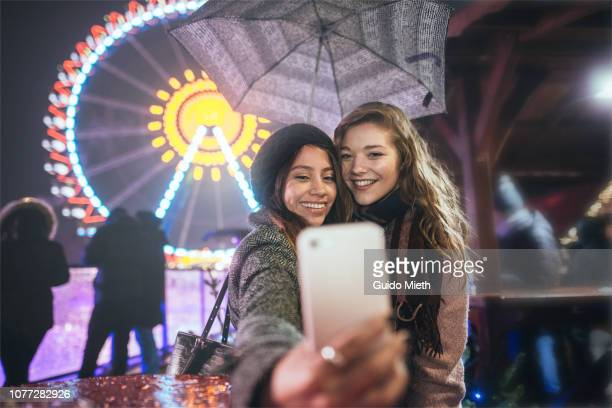 Friends taking a selfie at christmas market.
