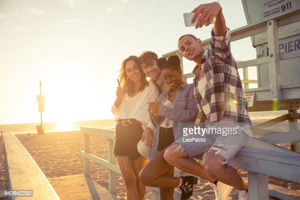 freunde nehmen eine selfie während einer party am strand von santa monica - los angeles - strandwächterhaus stock-fotos und bilder
