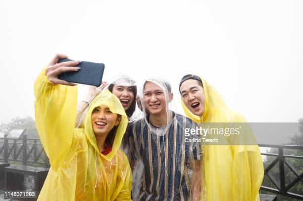 friends taking a selfie in the rain - poncho stock pictures, royalty-free photos & images