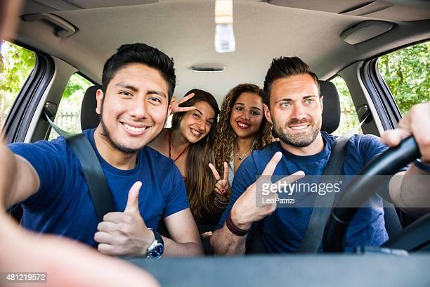 Friends taking a selfie on mobile inside the car