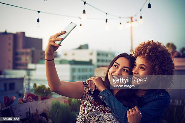 friends taking a selfie on urban rooftop - female friendship stock pictures, royalty-free photos & images
