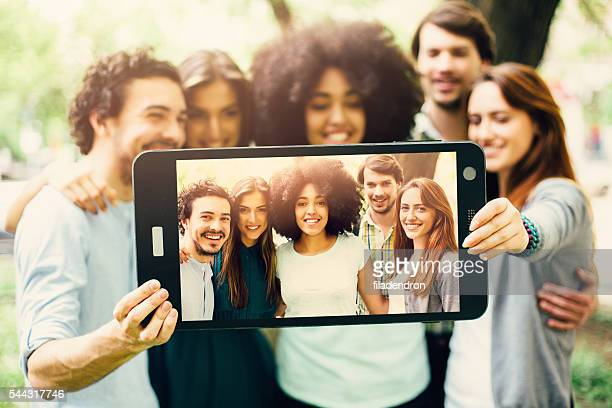 Friends taking a selfie with a large smart phone