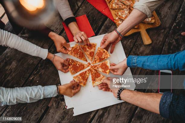 friends taking a slice of pizza from the pizza box - sharing stock pictures, royalty-free photos & images