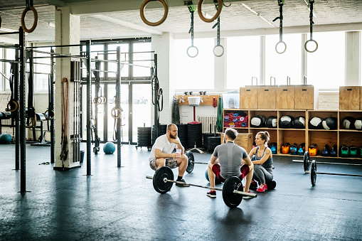 Friends Taking Break From Weight Lifting At Gym - gettyimageskorea