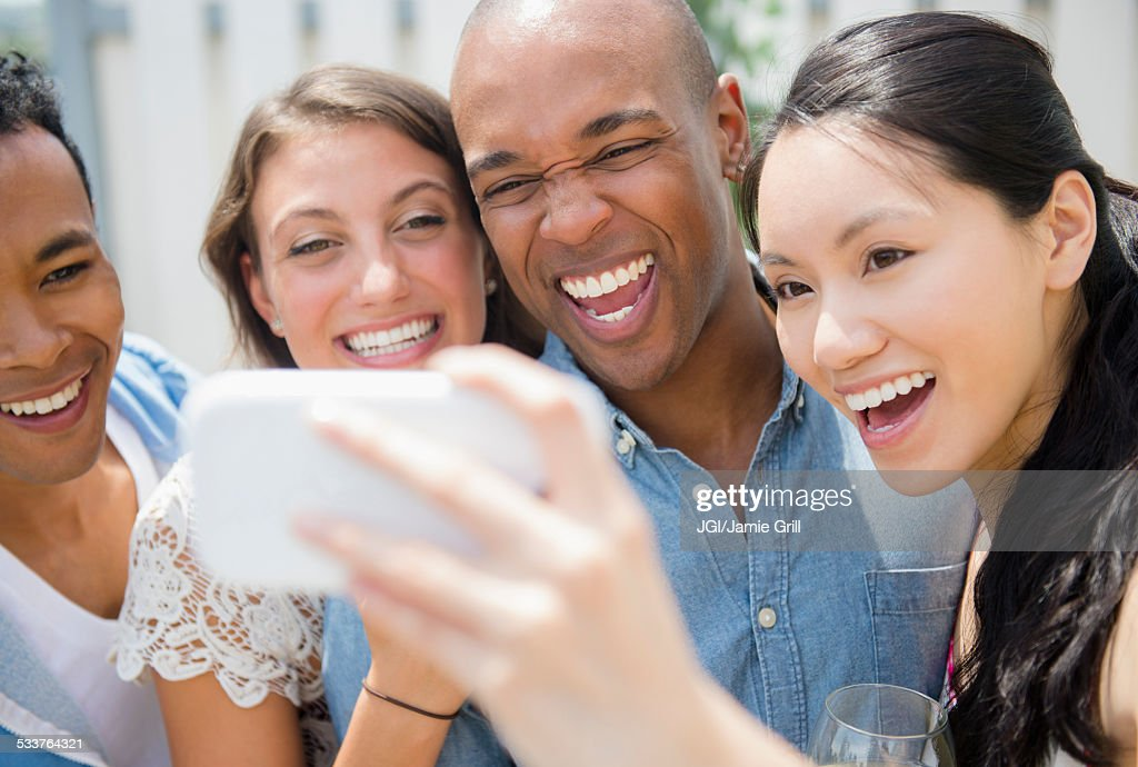 Friends taking cell phone photograph at party : Foto stock