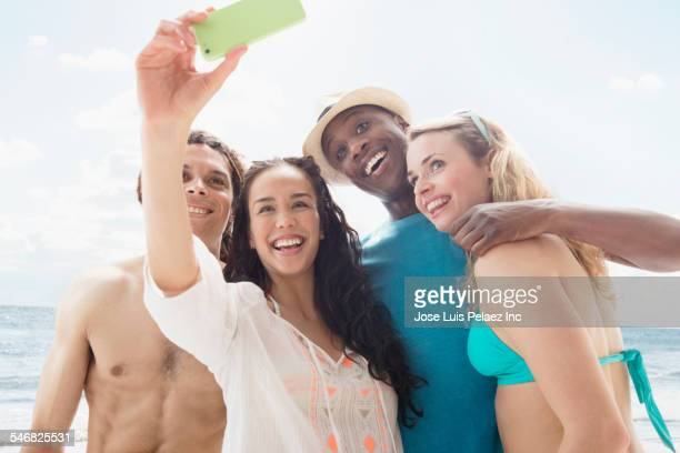 Friends taking cell phone photograph on beach