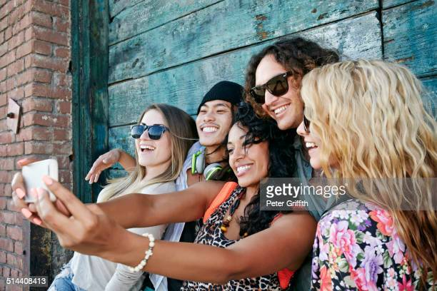 friends taking cell phone picture together on city street - multiculturalism stock pictures, royalty-free photos & images
