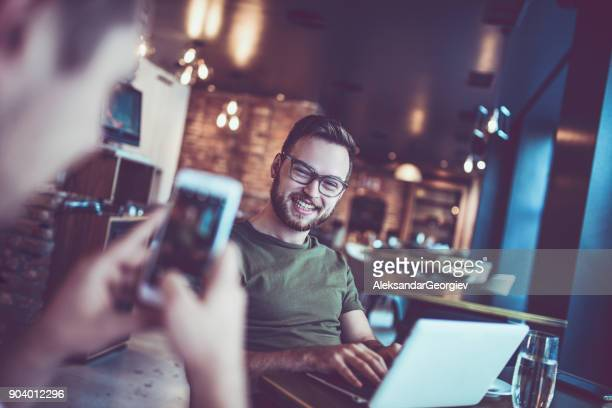 Friends Taking Photo of Smiling Hipster Freelancer how Working in Coffee