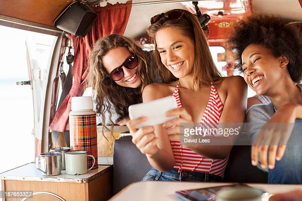 Friends taking photo of themselves in camper van