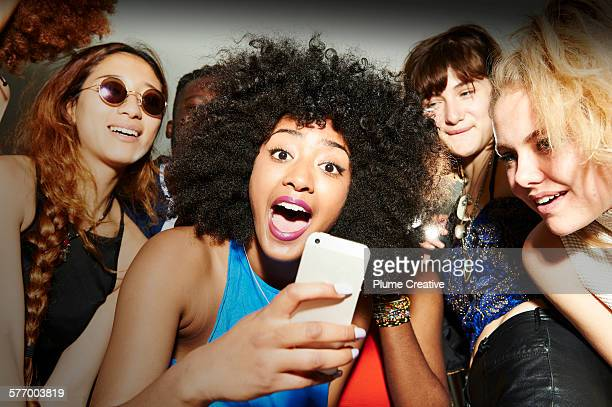 Friends taking photos at a party.