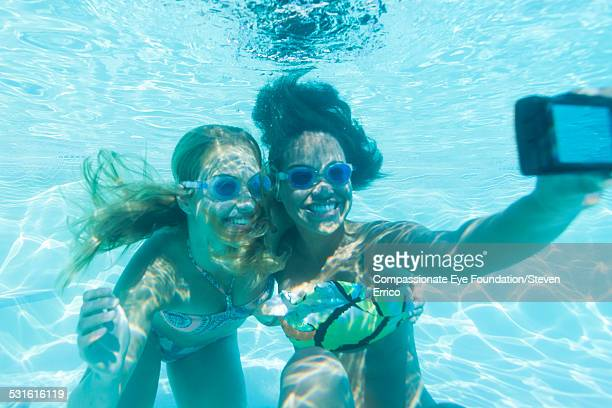 Friends taking picture of themselves underwater