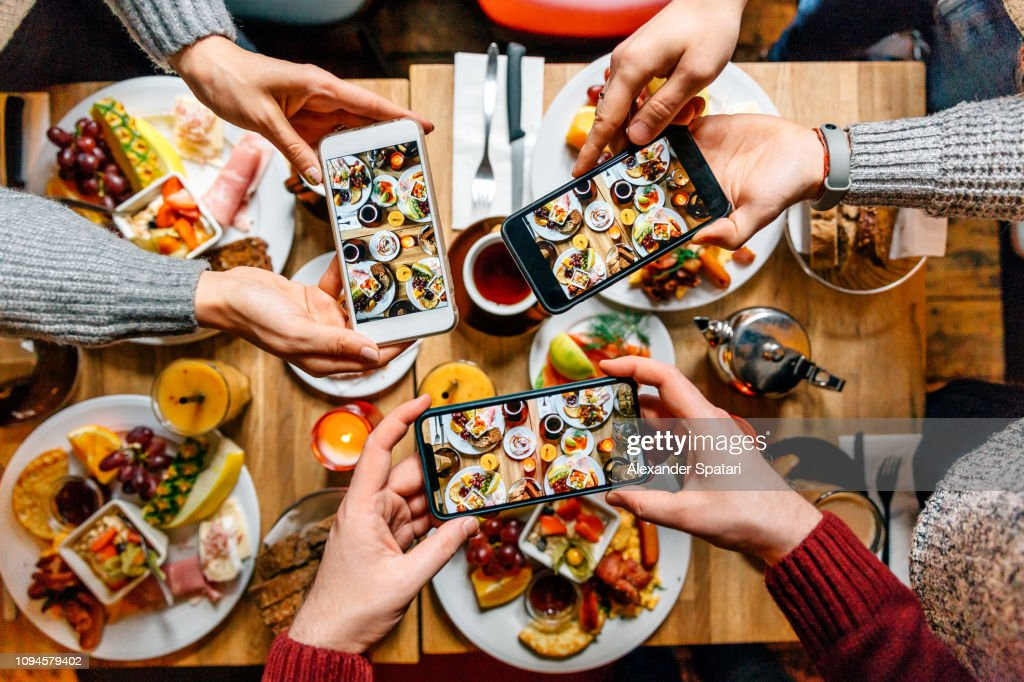 Friends taking pictures of food on the table with smartphones during brunch in restaurant : Stock Photo