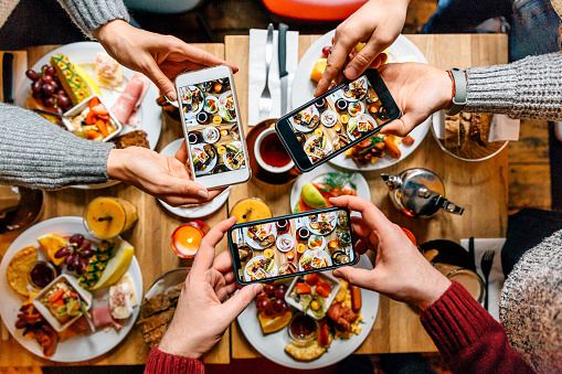Friends taking pictures of food on the table with smartphones during brunch in restaurant - gettyimageskorea