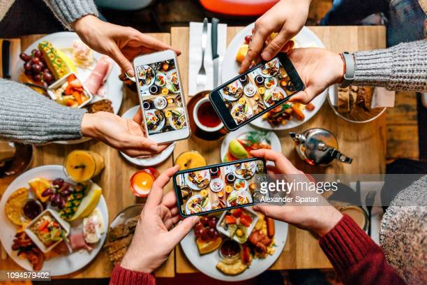 friends taking pictures of food on the table with smartphones during brunch in restaurant - food photos et images de collection