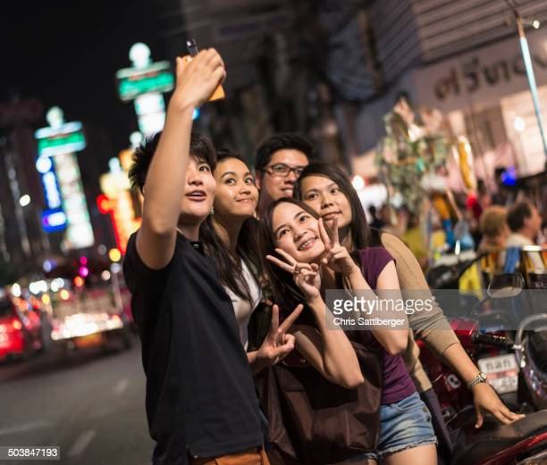Friends taking pictures on city street at night