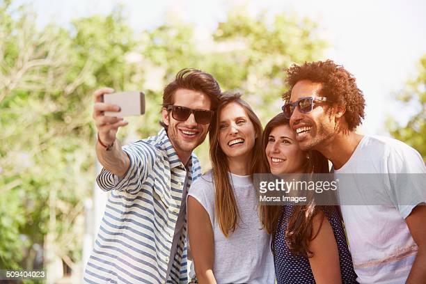 Friends taking self portrait through mobile phone