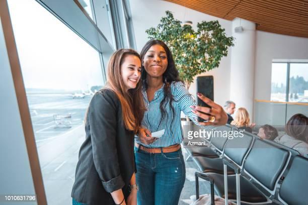 Friends taking selfie at airport departure area