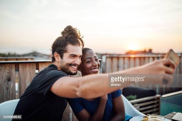selfie auf dachterrasse party unter freunden - heterosexuelles paar stock-fotos und bilder