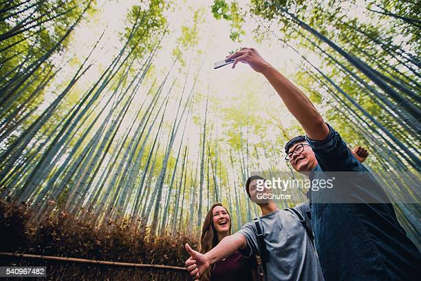 Friends taking selfie at the Bamboo Forest, Arashiyama, Kyoto, Japan