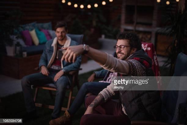 Friends taking selfie by the fire pit