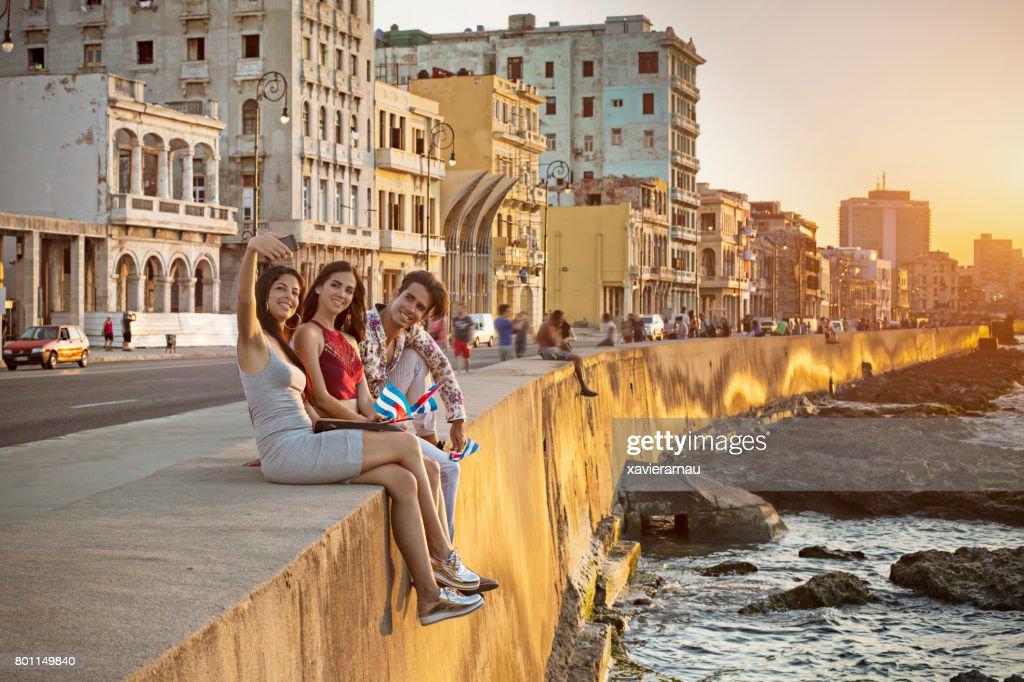 Friends taking selfie on retaining wall in Havana : Stock Photo