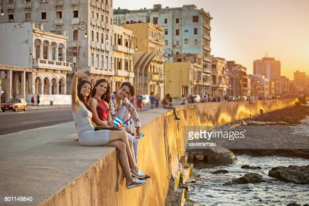Freunde nehmen Selfie auf Stützmauer in Havanna