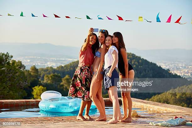 Friends taking selfie through smart phone on pool