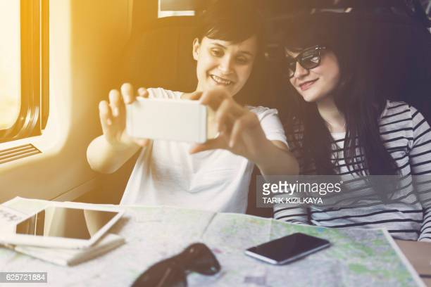 Friends taking selfie, travelling in a train