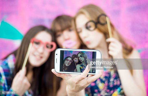 Friends taking selfie wearing fake spectacles and lips