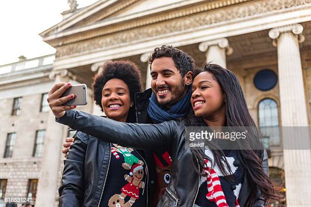 friends taking selfie while christmas shopping in ugly festive sweaters - ugly black women stock photos and pictures