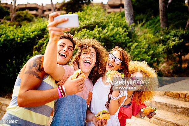 Amigos tomando autofoto con hamburguesas