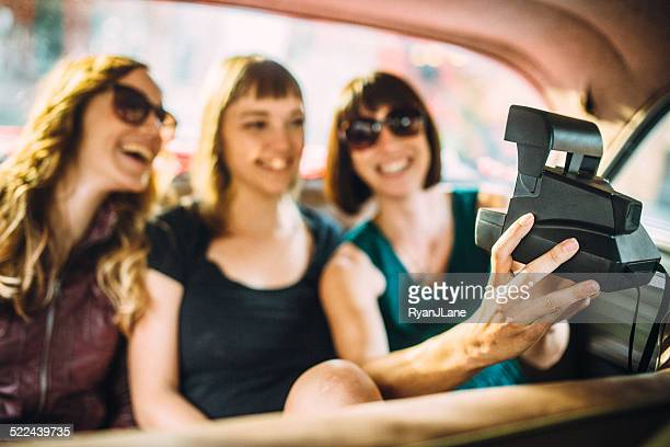 Friends Taking Selfie with Instant Camer