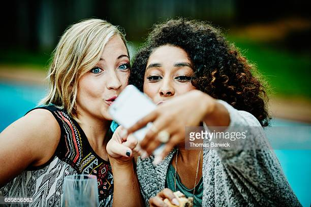Friends taking selfie with smartphone at party