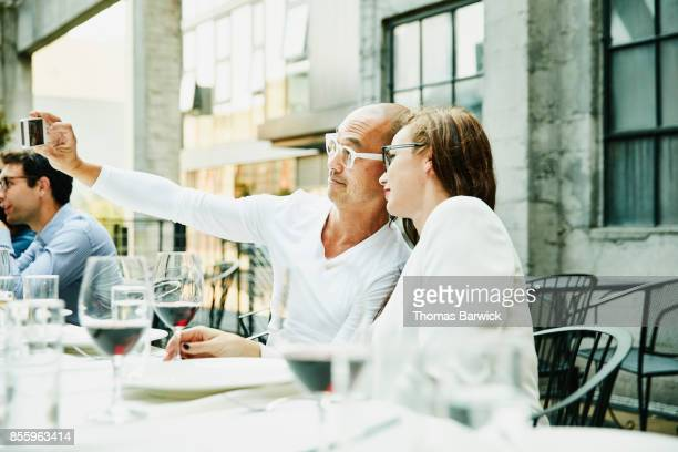 Friends taking selfie with smartphone during dinner on restaurant patio