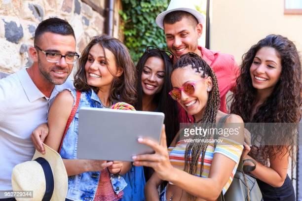 Friends taking selfie with tablet on street