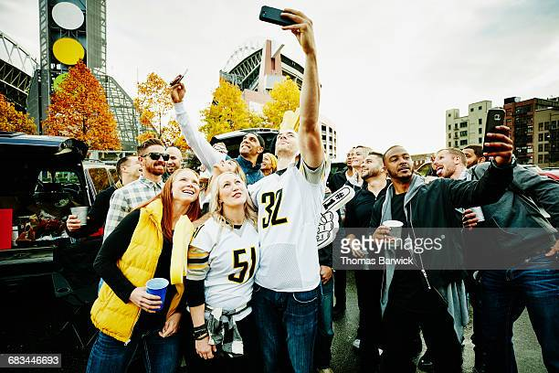 Friends taking selfies at tailgating party