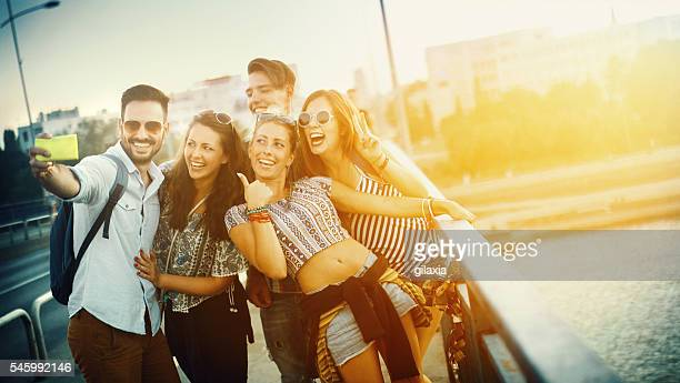 Friends taking selfies outdoors.