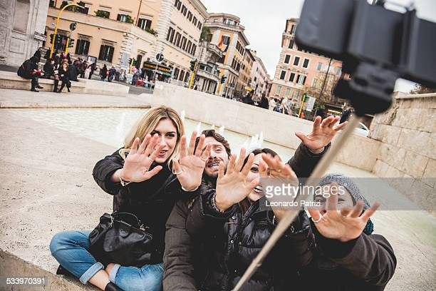 Friends taking selfies using a selfie stick in Rome near the Ara Pacis In Rome is not difficult at all find someone who resell this object