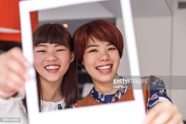 Friends taking selfies with a picture frame