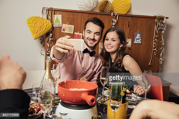 Friends taking selfies with smart phone on New Year's Eve