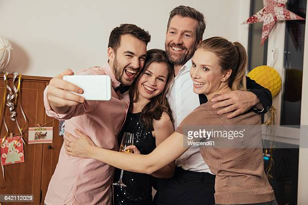 Friends taking selfies with smart phone on New Years Eve